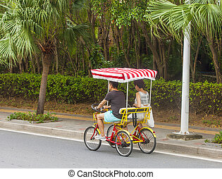 Men and women ride a four-wheeled bicycle