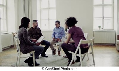 Men and women sitting in a circle during group therapy,...