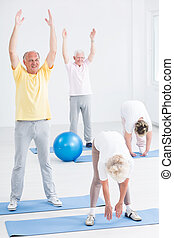 Men and women stretching at the gym