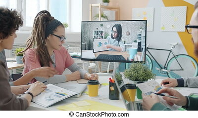 Men and women talking to female colleague online through video call in office
