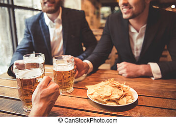 Men at the pub - Handsome businessmen are clinking glasses...