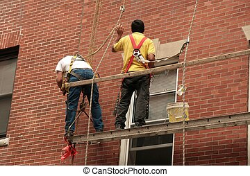2 men at work on scaffold with safety harnesses repairing brick mortar on a building in the city