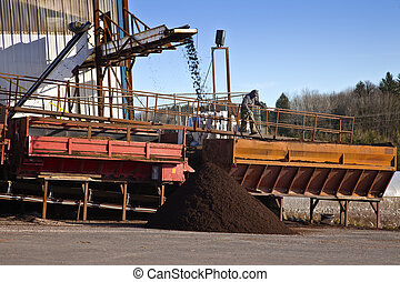 Men at work processing compost for agriculture.