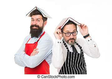 Men bearded apron reading book about culinary. Men in charge household. Some problems. Household duties. Book as roof on head. Household is boring. Who rules in house. Responsibilities of household