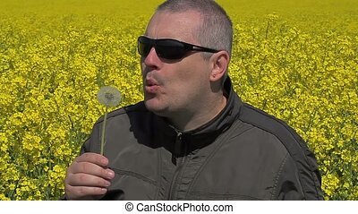 Men blowing dandelion