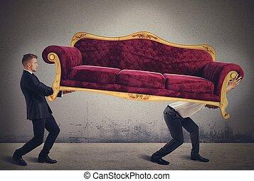 Men carrying a sofa - Men carrying a very heavy antique sofa
