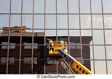Men cleaning windows - Men cleaning building's windows on a...