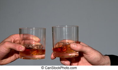 Men clinking whiskey glasses on grey background in slow motion