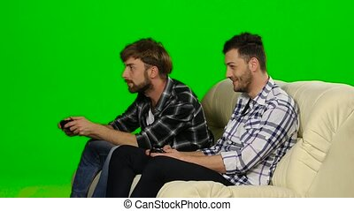 Men compete in the game on the console. Green screen - Men...