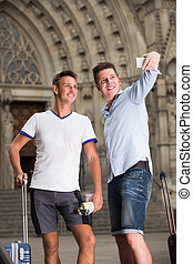 Men couple with luggage doing selfie at travel