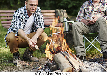 Men crouching next to bonfire in forest