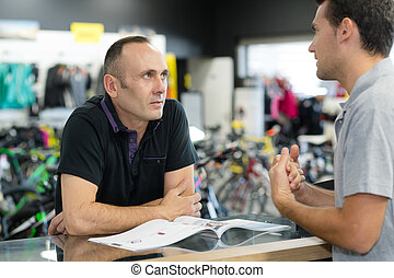 men discussing in bicycle store