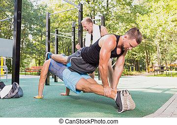 Men doing push-ups in a park