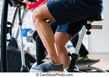 Men doing workout on exercise bike at gym