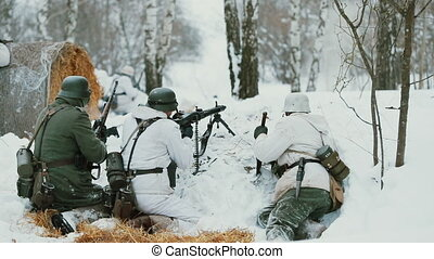 Men Dressed As German Wehrmacht Infantry Soldiers In World War II Hidden Sitting With Weapon In An Ambush And Aiming a Machine Gun at Enemy From Trench In Winter Day. Slow Motion.