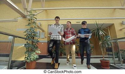 Men dressed in checkered shirts walk through shopping mall.