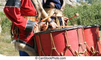 Men dressed in historical costumes of the ancient Scythians play the drums.