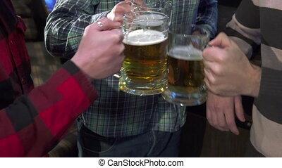 Men drink lager near the bar counter - Three men drinking...