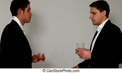 Men drinking whiskey shaking hands