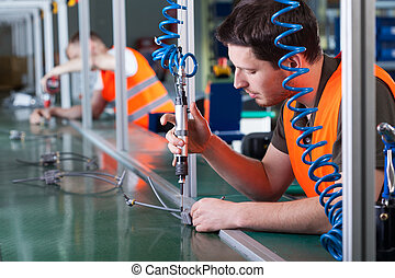 Men during precision work on production line, horizontal