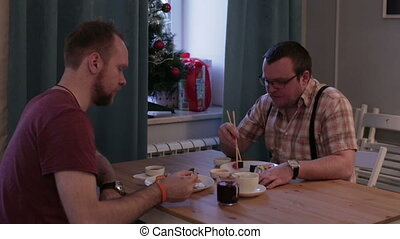 Men eating sushi at the table