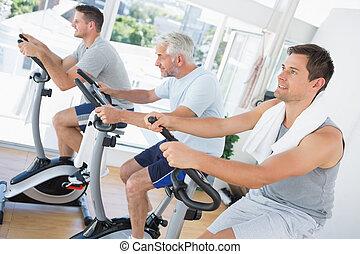 Men exercising on fitness bikes