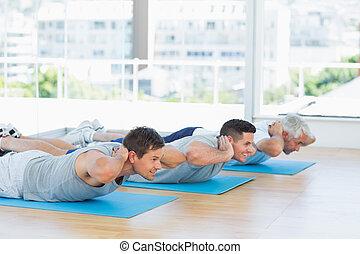 Men exercising on mats at gym