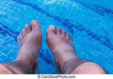 Men feet in a swimming pool