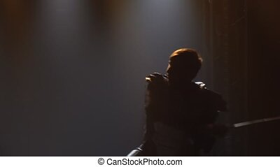 Men fight with swords in a dark studio with stage lighting. Silhouettes of male actors in armor performing in a theatrical show. Close up in slow motion