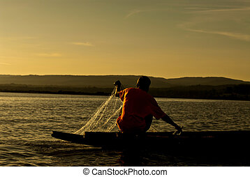 Men fishing on the Mekong River in a field at sunset, Chiang Khan, Thailand
