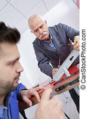 Men fitting new door lock to interior door