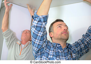 Men fitting plasterboard to ceiling
