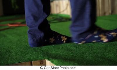 Men foot on green doormat. Men's feet in socks on a green...