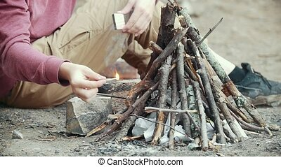 Men hand with a match lights a branches into small bonfire in the forest