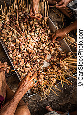 Men hands preparing a balinese traditional sate for cooking. Bali island.