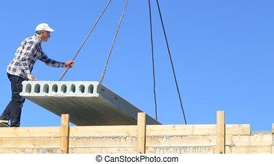 Men hang a concrete slab on a mobile crane - Men cling a...