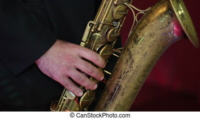 men in a black jacket  playing the old saxophone