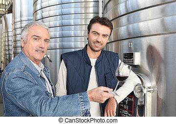 Men in a modern wine making facility