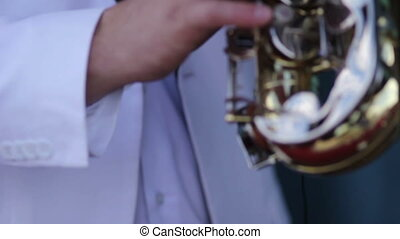 men in a white jacket  playing the saxophone