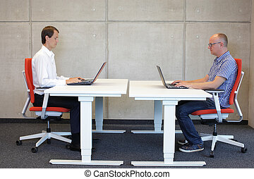 men in correct sitting posture - two men working in correct...