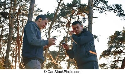 men in earphones is having rest and listening to music during listening to music on headphones on a smartphone running outdoors near modern private houses. men group running in the nature sports lifestyle