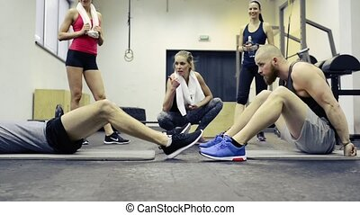 Men in gym doing crunches with medicine balls. - Two young...