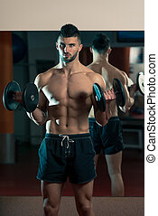 Men In Gym Exercising With Dumbbells