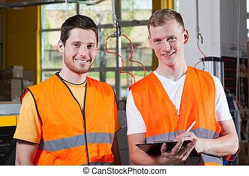 Men in orange protective vest working at factory