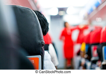 men in plane seat looks at the airhostess explain at the front of the row.