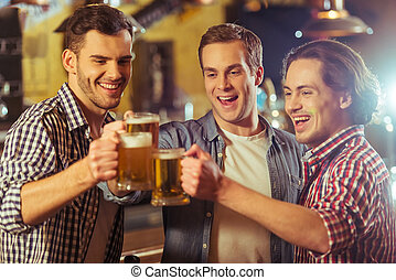Men in pub - Three young men in casual clothes are smiling...