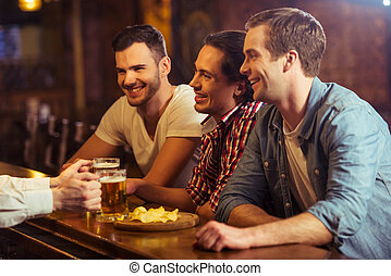 Men in pub - Three young men in casual clothes are talking...