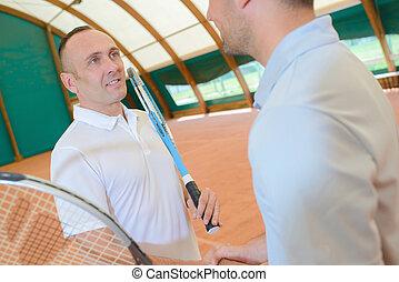 men in the tennis court