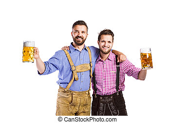 Men in traditional bavarian clothes holding mugs of beer - ...
