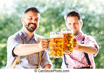 Men in traditional bavarian clothes holding mugs of beer -...